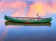 Grünes Fischen-Kanu an der Dämmerung stockfoto