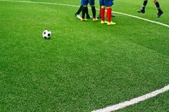 Grünes Fußballplatzgras mit weißer Kennzeichenlinie und die Jungen spielen Fußballhintergrund stockfotografie