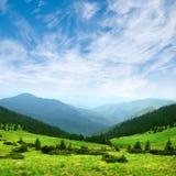 Grünes Gebirgstal und -himmel Stockfoto