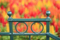 Grünes Geländer mit bunten unscharfen Blumen im Hintergrund Stockfotos