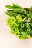 Grünes Gemüse in der hölzernen Platte auf hölzernem Hintergrund Lizenzfreie Stockbilder