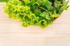 Grünes Gemüse in der hölzernen Platte auf hölzernem Hintergrund Stockbilder
