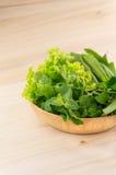 Grünes Gemüse in der hölzernen Platte auf hölzernem Hintergrund Lizenzfreies Stockbild