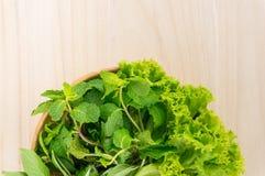Grünes Gemüse in der hölzernen Platte auf hölzernem Hintergrund Stockfotos