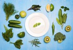 Grünes Gemüse trägt und Kräuter um weiße Platte auf hölzerner Querstation Früchte Stockfotos