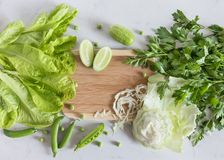 Grünes Gemüse und hölzernes Schneidebrett auf einer hellen Oberfläche Lizenzfreie Stockfotografie