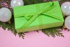 Grünes Geschenk mit Tupfenband auf Rosa Stockfoto