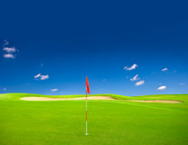Grünes Golffeld mit blauem Himmel stockfotos