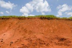 Grünes Gras auf Lehmhügel und blauen Himmel Stockfotografie