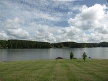 Grünes Gras, das zu den See führt Lizenzfreie Stockbilder