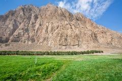 Grünes Gras mit Brunnen für Bewässerung im Gebirgstal Lizenzfreies Stockfoto