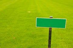 Grünes Gras mit einem Zeichen, horizontaler Schuß Lizenzfreie Stockbilder