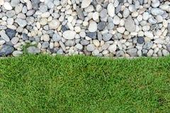Grünes Gras mit Kieseln, Stein und Gras im Garten, Gras mit Felsen, Kiesel mit Gras Lizenzfreie Stockbilder