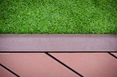 Grünes Gras mit redwalkway Hintergrund Stockbild