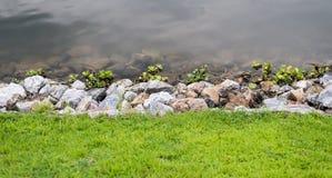 Grünes Gras mit Steinen und Wasser Stockbild