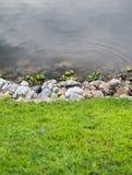 Grünes Gras mit Steinen und Wasser Lizenzfreies Stockfoto