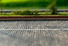 grünes Gras und Bürgersteig der Neigung-Schiebepflastersteinstraße hinter Bus Stockfoto
