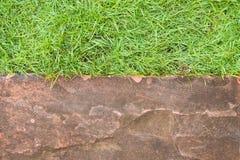Grünes Gras und orange, Brown-Laterite Ziegelstein Stockfotos