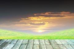 Grünes Gras und orange Himmel mit hölzernem Stockfoto