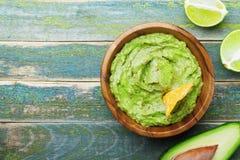 Grünes Guacamole mit Bestandteilen Avocado, Kalk und Nachos auf hölzerner Weinlesetischplatteansicht Traditionelles mexikanisches stockfotografie