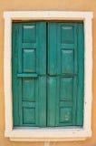 Grünes hölzernes Fenster auf der orange Wand Lizenzfreies Stockfoto