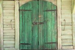 Grünes hölzernes Tor eines Scheunengebäudes stockbild
