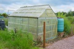 Grünes Haus des Zuteilungsgartens mit Wasserkolben Stockbild