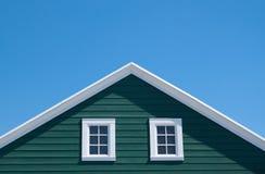 Grünes Haus und weißes Dach mit blauem Himmel Stockbild