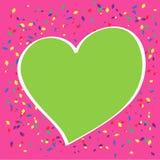 Grünes Herz auf rosa Hintergrund Stockbild