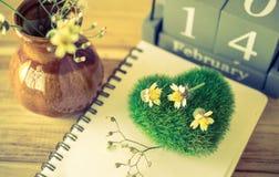 grünes Herz mit hölzernem Kalender der Weinlese für den 14. Februar, noteboo Stockbilder