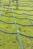 Grünes Jagdnetz auf dem kletternden Rahmen eines Kindes lizenzfreie stockfotos