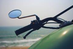 Grünes königliches Enfield-Motorrad durch den Ozean in Indien Stockfotografie