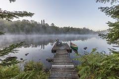Grünes Kanu und Dock auf einem nebelhaften Morgen - Ontario, Kanada Stockfoto