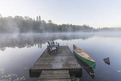 Grünes Kanu und Dock auf einem nebelhaften Morgen - Ontario, Kanada Lizenzfreies Stockfoto