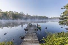 Grünes Kanu und Dock auf einem nebelhaften Morgen - Ontario, Kanada Lizenzfreies Stockbild