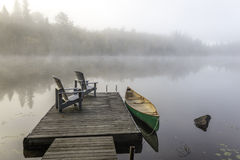 Grünes Kanu und Dock auf Misty Morning Stockfotos