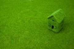 Grünes kleines Haus auf grünem Gras Lizenzfreie Stockbilder