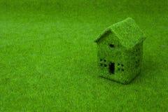Grünes kleines Haus auf grünem Gras Stockbild