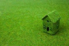 Grünes kleines Haus auf grünem Gras Stockfotografie