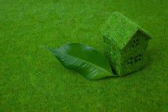 Grünes kleines Haus auf grünem Gras Stockfotos