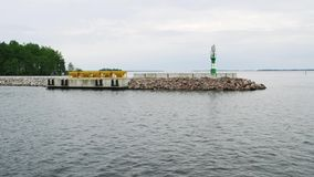 Grünes Leuchtfeuer auf felsigem Pier stock footage