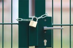 Grünes Metalltor, verschlossen mit Kette und Vorhängeschloß stockfotografie
