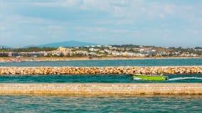 Grünes Motorboot, das den Hafen in Lagos, Portugal betritt lizenzfreies stockbild