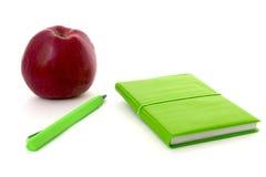 Grünes Notizbuch und Apfel lokalisiertes Weiß Lizenzfreie Stockfotografie