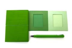Grünes Notizbuch- und Stiftweiß Stockfotos