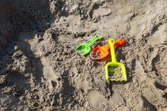 Grünes, orange, gelbes Plastikspielzeug schaufelt auf dem Strandsand oder dem Sandkasten stockbilder
