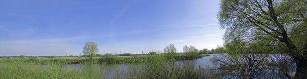 Grünes Panorama mit Fluss und blauem Himmel lizenzfreies stockfoto
