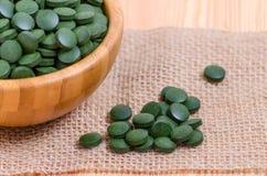 Grünes Pillen spirulina und Chlorellameerespflanzenabschluß oben auf dem hölzernen Lizenzfreies Stockbild