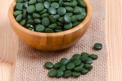 Grünes Pillen spirulina und Chlorellameerespflanzenabschluß oben auf dem hölzernen Hintergrund Lizenzfreie Stockfotos