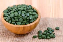 Grünes Pillen spirulina und Chlorellameerespflanzenabschluß oben in einer hölzernen Schüssel Lizenzfreie Stockbilder